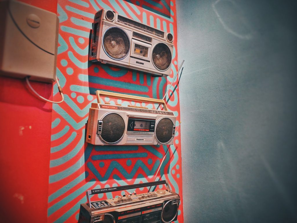 Old-school boomboxes hanging on wall with patterned designed in red and blue