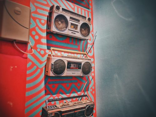 Old-school boomboxes line a decorative, patterned wall