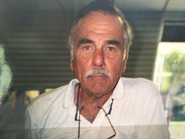 an elderly man gazes into the camera