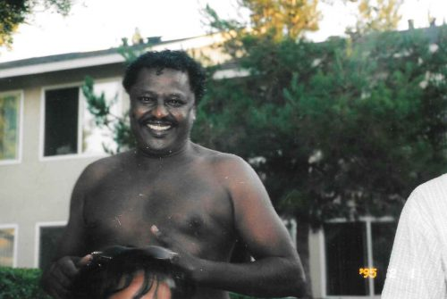 a dark-skinned Sudanese man smiles into the camera after coming out from a swim