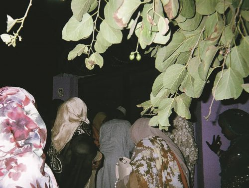 a group of Sudanese women walk through purple doors in the evening