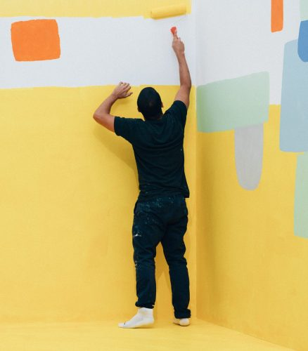 Federico Herrero, seen from the back, in a corner of a room painting the wall in bright yellow.