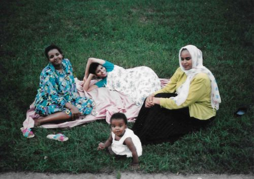 three Sudanese women and a baby lounge on a pink blanket on a lawn