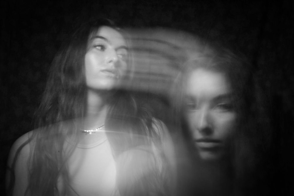This black and white image features the same fair skinned female. On the left side of the image she sits looking across the frame. Coming from her face are motion blur streaks which lead to a ghostly image of her face in the right bottom corner of the frame.