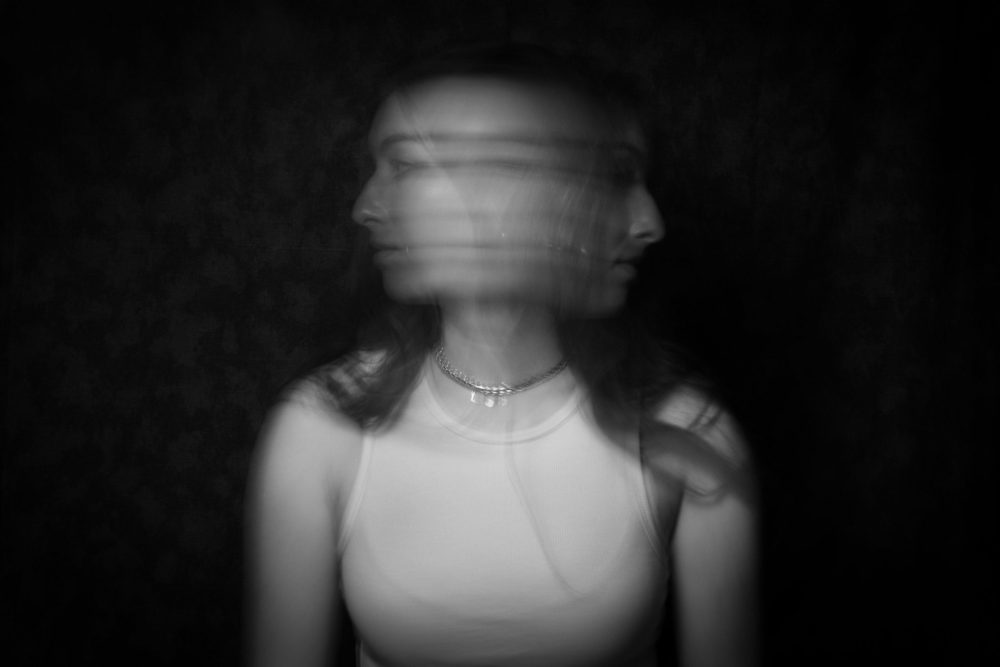 This black and white image features a fair skinned female from the torso up. Her face is obscured by motion blur, her head has a face profile on both sides. Background is dark grey and ominous.