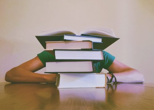 A person sitting behind a stack of books