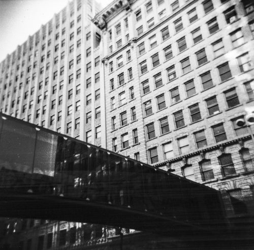 A side shot of a old building, with a walkway tunnel in black and white.