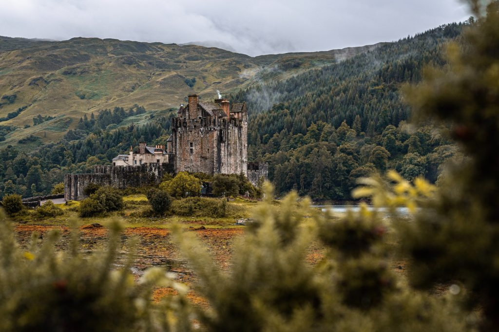 A castle in a clearing in front of the wooded hills of the Scottish highlands.