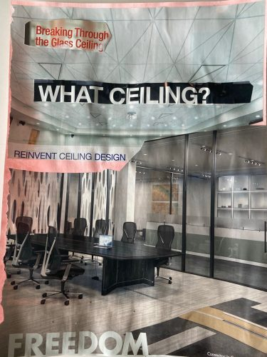 """A collaged image of an office space appears with various sections of found text. On the top left, a clipped fragment of text says, """"Breaking through the glass ceiling"""" in red ink on white paper. A few lines below, in large white letters on a black background, a clipped fragment of text reads: """"What ceiling?"""". Below and to the left, the text reads: """"Reinvent Ceiling Design,"""" and at the bottom in large capital letters: """"Freedom."""""""
