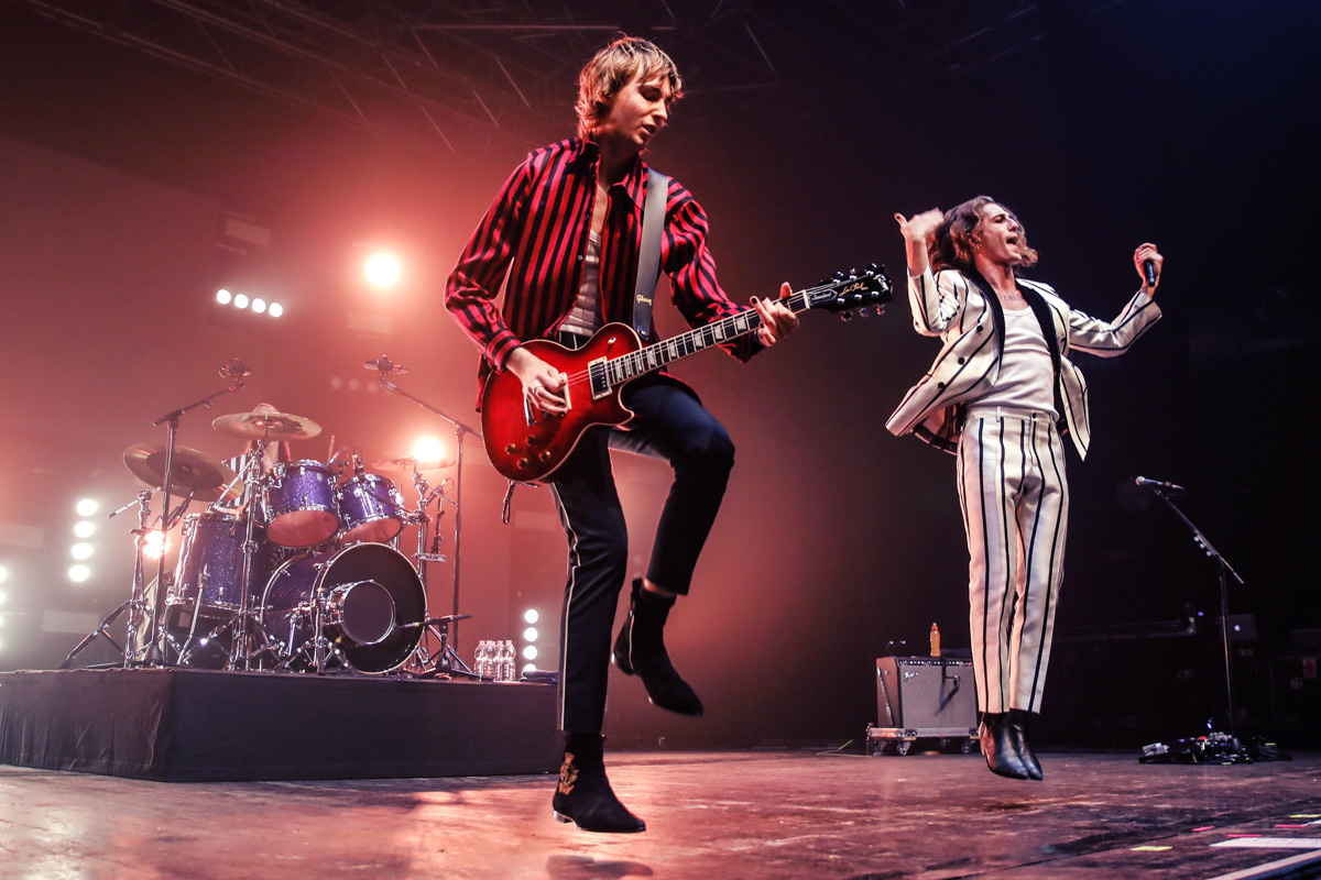 Maneskin performing on stage. A performer dressed in a striped white black suit is midair. The guitarist, wearing a black and white, striped shirt and dark pants, plays the guitar. The drummer is in the background.