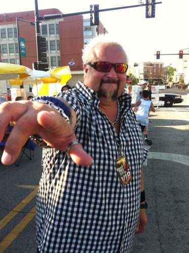 Guy Fieri points toward camera with index finger, wearing sunglasses and a sly smile