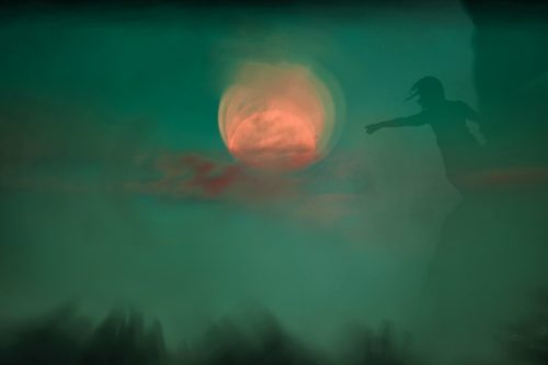 a photograph of a silhouette stretching an arm out toward an orange moon against a green background and sky