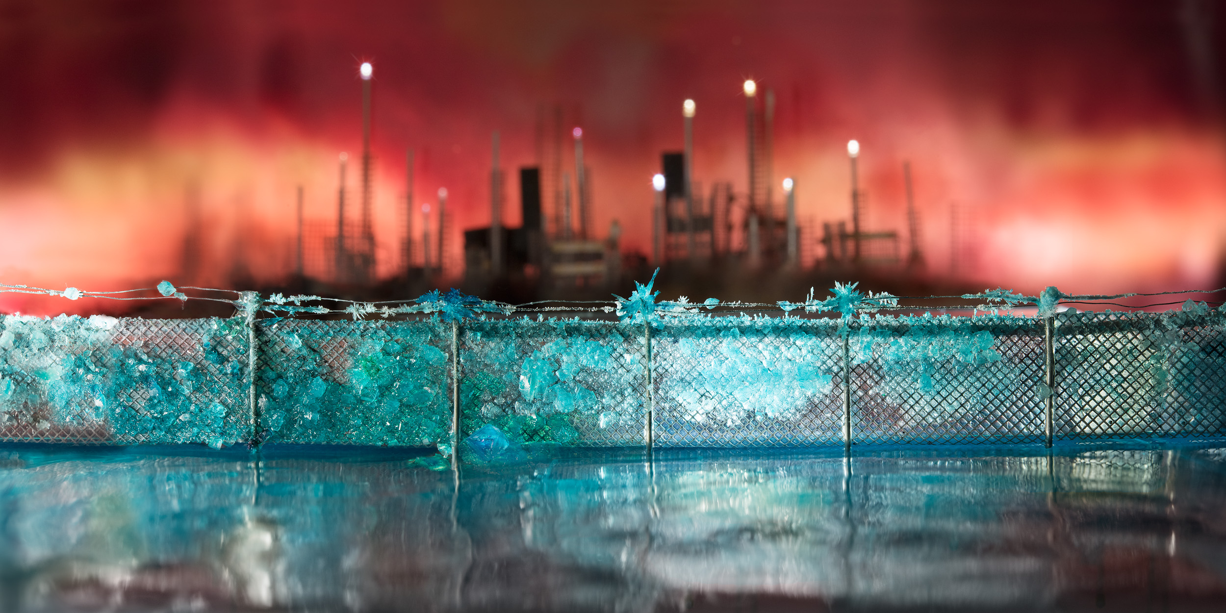 Print of bright blue crystals growing along a barbed wire fence, in front of a blurry, distant, industrial cityscape and a red-orange sky.