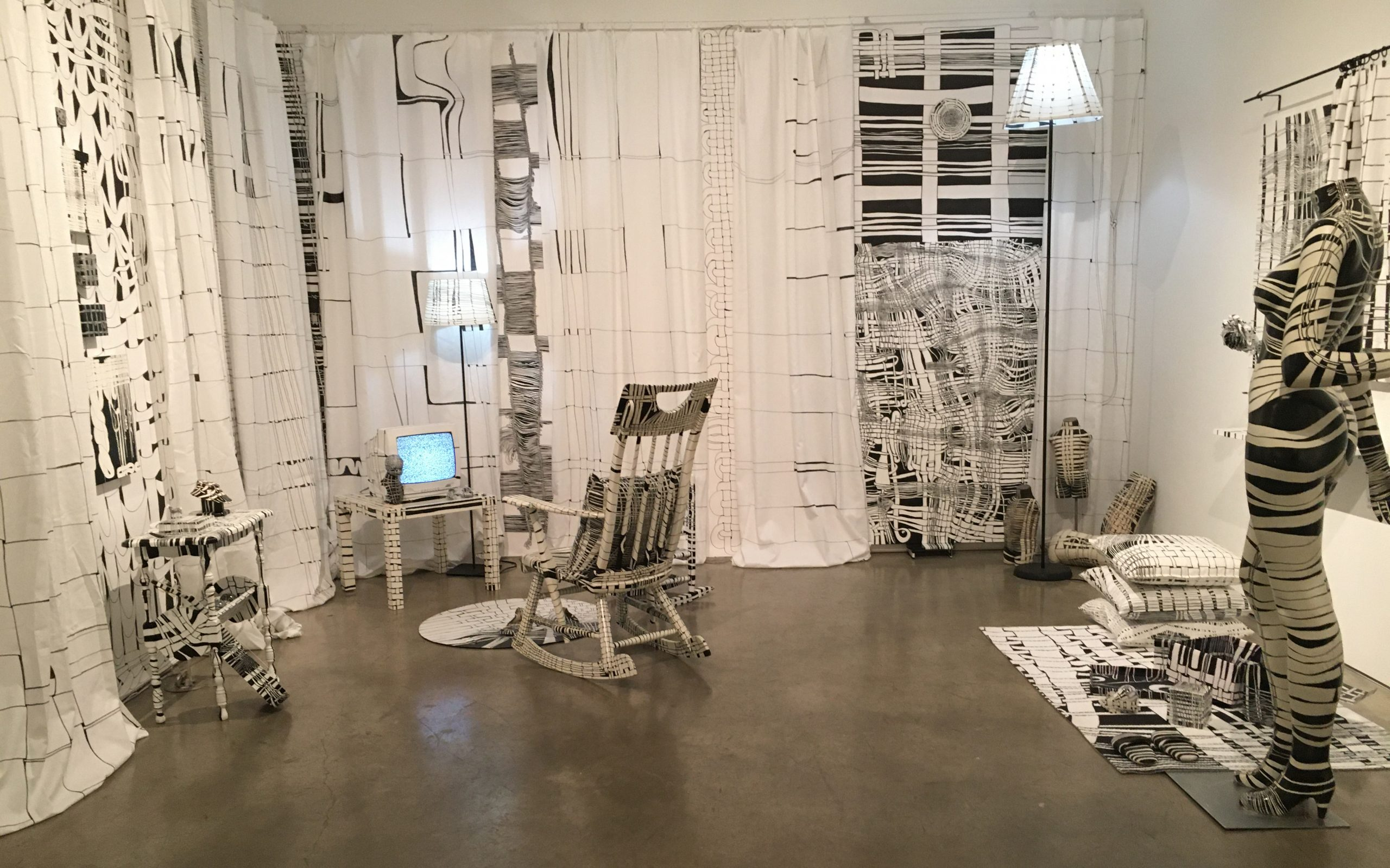 a color photograph of a white room filled with white furniture drawn on with thin and thick lines of black ink