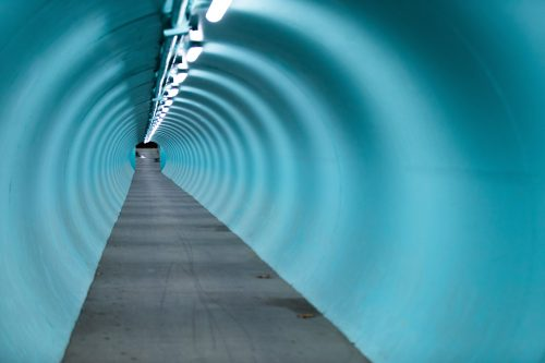 a color photograph of a blue tunnel lit by a line of fluorescent lights casting multiple ringed shadows down to the distant exit