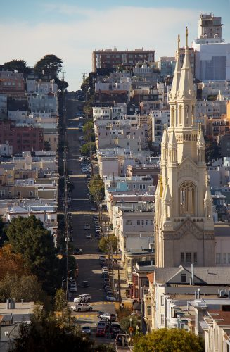 Color photograph of a steep hill in San Francisco with cars, houses, and a church.
