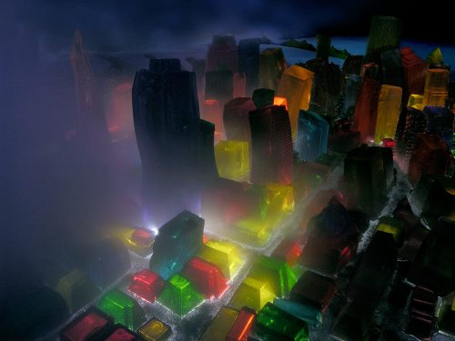 Bright yellow, red, green, blue, and orange jell-o structures replicate San Francisco in low lighting. The bay and bridges can be seen in the distance. On the left side of the frame, fog rolls in.