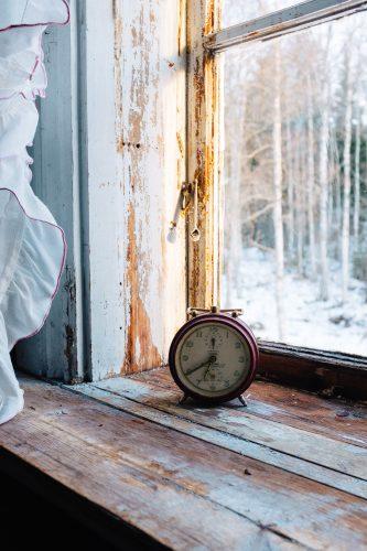 Photograph of red analog alarm clock beside window