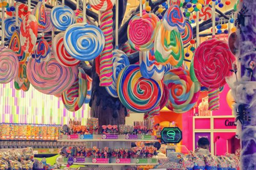 color photograph of a candy store with colorful lollipops hanging from the ceiling