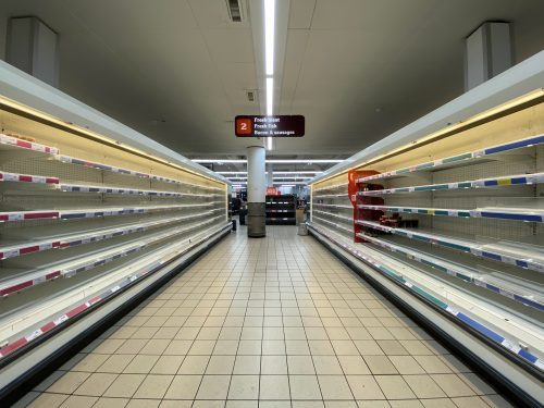 Picture of a grocery aisle with empty shelves